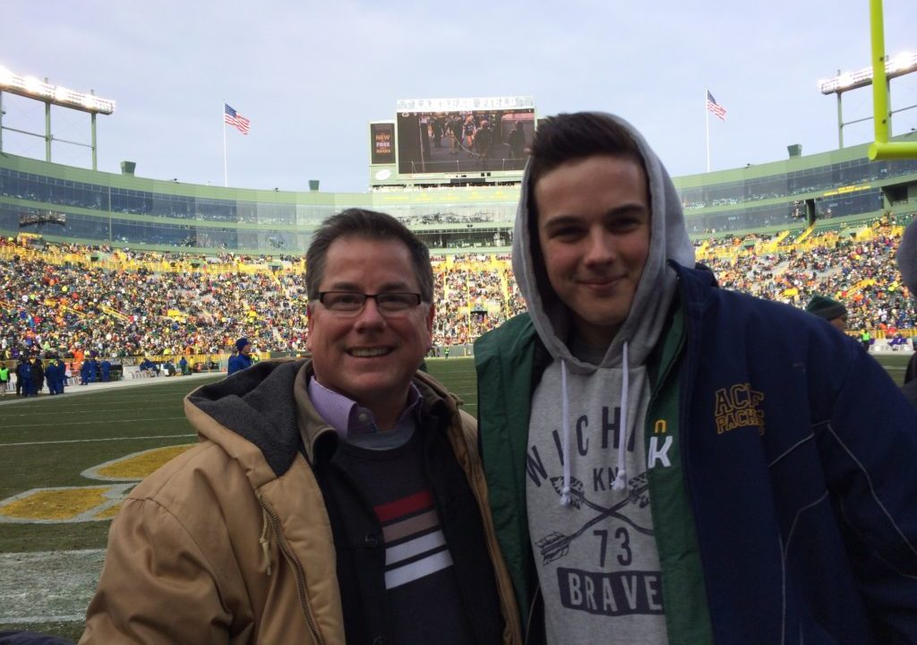 John and his son John on the field at a Packers game.